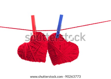 two thread hearts on a red string isolated on white background