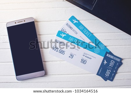 Two tickets are on the table with a phone and laptop. The concept of buying the online ticket booking for travel #1034164516