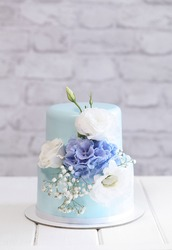Two Tier Wedding Mini Cake decorated with fresh flowers, on a gray brick wall background.