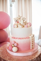 Two-tier white pink cake with number one, little bear, white and pink balls and golden stars on a table with a sparkle tablecloth. Concept of a birthday cake for a girl on her first birthday.
