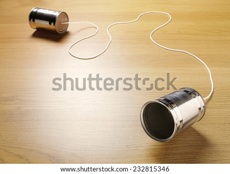 Two tin cans joined with a cord on a wooden background for primitive communication.