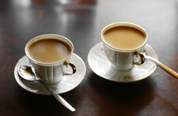 two tiny coffee cup with hot milk coffee and teaspoons on the table close up photo