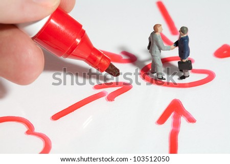 Two tiny miniature businessmen giving a business handshake sealing the deal standing in a schematic handrawn diagram of converging arrows with fingers holding a red marker pen for scale comparison