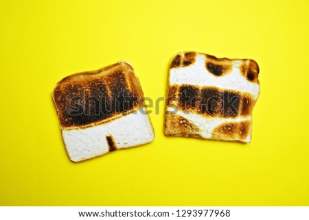 Two toasts are on a colorful background - both are not toasted all over the surface but show the contours of bathing trunks and bikini - concept of sunburn pictured with toasts #1293977968