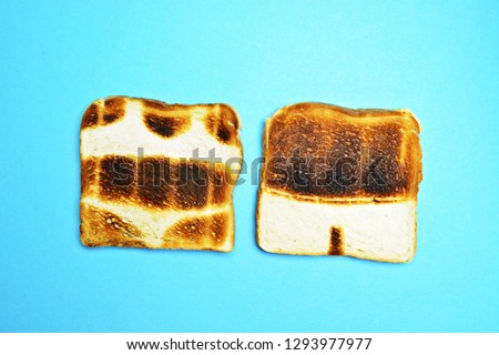 Two toasts are on a colorful background - both are not toasted all over the surface but show the contours of bathing trunks and bikini - concept of sunburn pictured with toasts #1293977977