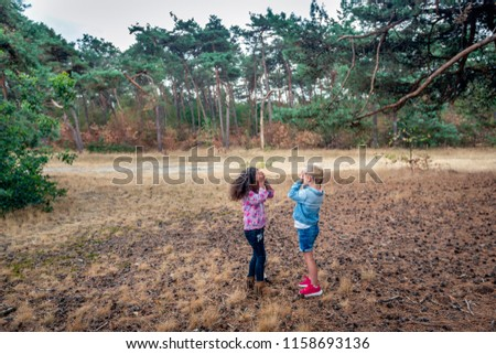 Two toddler girls put their hands before the eyes and count to twenty during a hide-and-seek game at an open place in the forest.