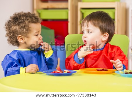 Two toddlers eating fruit in a nursery