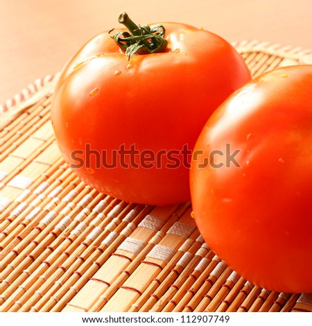 Two tomatoes on the rattan tray