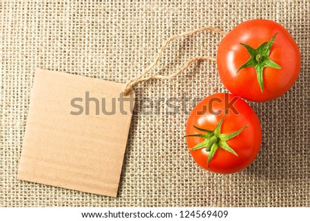 two tomatoes with cardboard tag on sacking