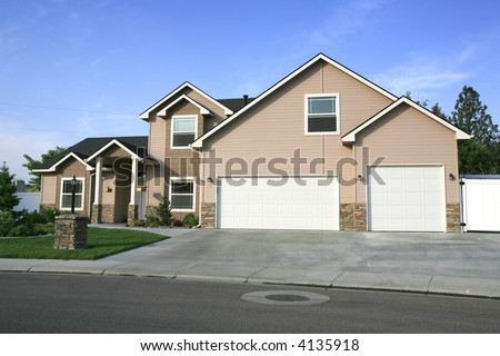 Two tone beige two story home with three car garage