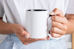Two tone black and white mug mockup for presentation sublimation designs. Stock photos of white coffee mug in the female hands  for designers