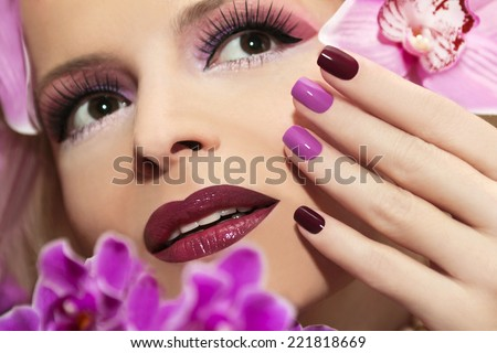 Two-tone manicure and Burgundy lilac makeup on the girl with orchids.