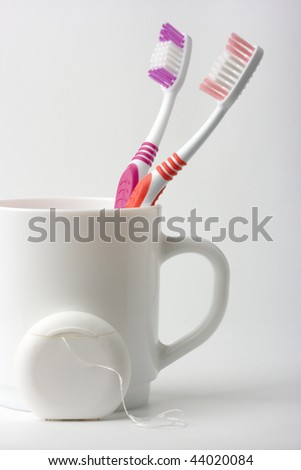 Two toothbrushes in a cup and dental floss - common toiletries