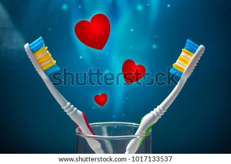 Two toothbrushes on a blue background and a lot of red hearts. Love and Valentine's Day. Copy space #1017133537