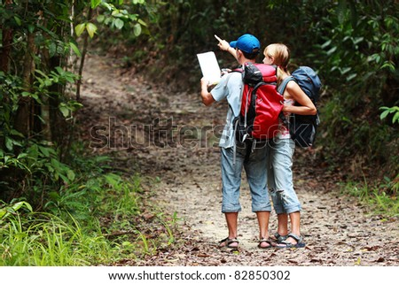 Two tourist looking for a road with map and clock in the forest with backpack