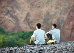 Two tourist young men sitting on rocky cliff and enjoying beautiful view