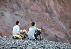 Two tourist young men sitting on rocky cliff and enjoying view