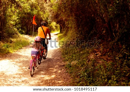 Two tourists, father and daughter, going in bycicles in touristic itinerary of national forest park Punta Corrente, Zlatni Rt, -- Rovinj, Croatia #1018495117