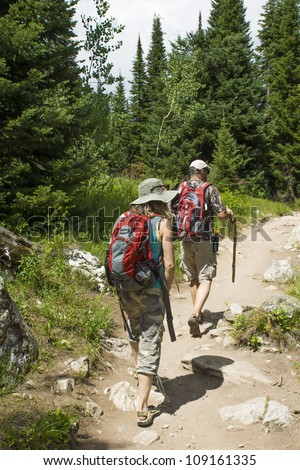 Two tourists make hiking the trail in the woods