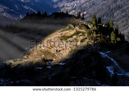 Two tourists walking on the touristic path lit by a beam of light in French Alps