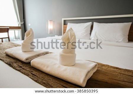 Two towels on the bed in hotel room.