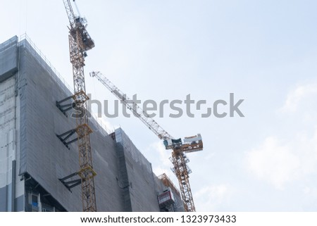 Building of a skyscraper with two tower cranes Images and