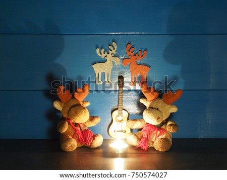 Two toy Christmas moose, or elks, are sitting on a background of blue wall with a candle, a guitar and romantic silhouettes in wooden rural house; very big shadows