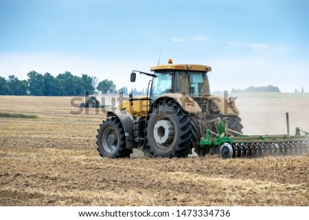 Two tractors cultivating the wheat field in summer
