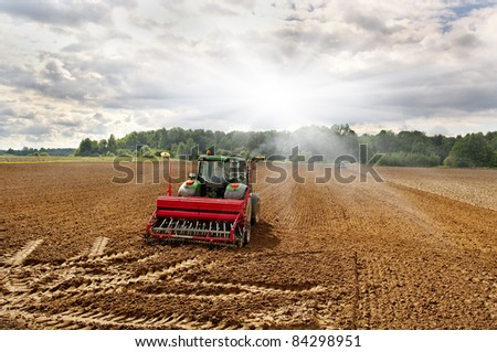 Two tractors on the field in a sunny day. - stock photo