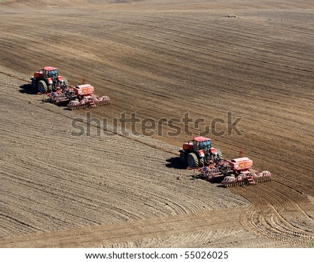 Two tractors plowing and sowing in the field - stock photo