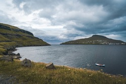 Two traditional boat with fisherman in a natural harbour, Faroe Island