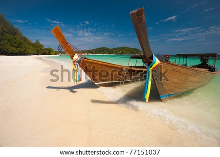 Two traditional longtail boats parked on a white sand beach surrounded by crystal clear turquoise water on the paradise island of Koh Lipe, Ko Lipe, Thailand