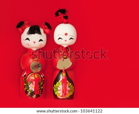 Two traditional wooden Chinese dolls against red background
