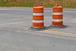 Two traffic safety barrels on an asphalt street, road construction barriers, horizontal aspect