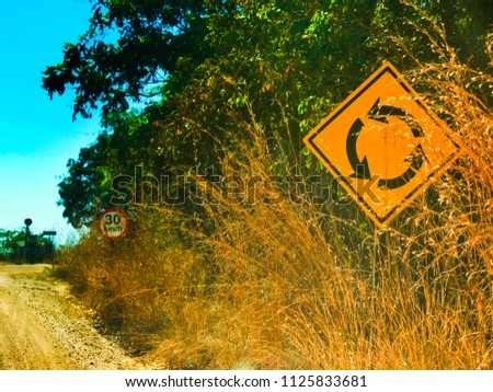 Two traffic signs on a dirt road, with dry vegetation and green vegetation. #1125833681