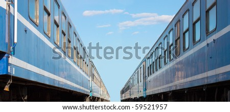 Two trains at the train station with blue sky background.