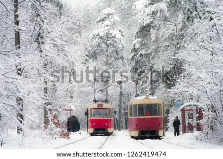 Two trams met at a tram stop in the winter forest. Selective focus. #1262419474