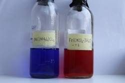 Two transparent glass bottles with reagents: blue nickel complex compound hexaamminenickel chloride, and red aqueous solution of ferric thiocyanate hydrate, with  chemical formulas.
