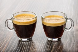 Two transparent glass cup with coffee espresso on dark wooden table