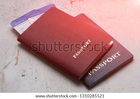 Two travelers passports red and blue with boarding passes for the plane. Travel concept Selective focus