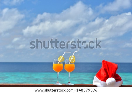 Two tropical fresh juices with santa hat on the tropical sea background -- Christmas vacation concept