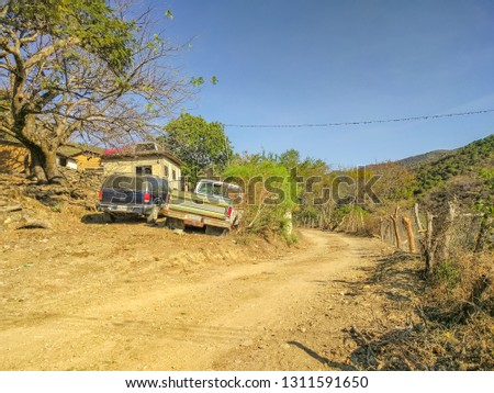 Two trucks are parked roadside along a dirt road unpaved road in Pipincatla of Ixcateopan. Rural streets in Guerrero. Travel in Mexico. Sierra Madre del Sur. #1311591650