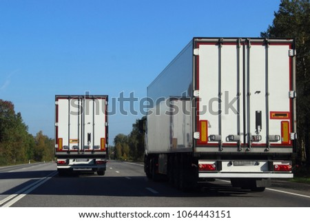 Two trucks on the road in summer against the blue sky #1064443151