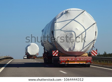 Two trucks with a police escort car carrying oversized cargo on the asphalt road in the summer against the blue sky #1064444312