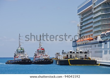 Two tugboats and a barge tied up to a cruise ship