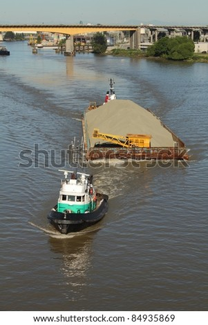 Two tugboats maneuver a barge full of sand up the north arm of the Fraser River near the Oak Street Bridge. Vancouver, British Columbia, Canada.