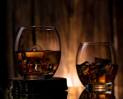 Two tumble glasses with ice cubes and alcohol. Back light showing the golden colour of the drink and a shine on the rim of glass. A moody shot.