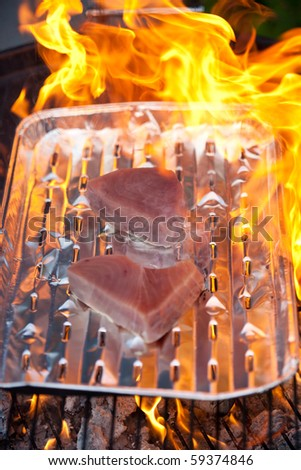 Two tuna steaks on a silver tray on a BBQ