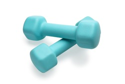 Two turquoise colored rubber dumbbells lying at white table close-up