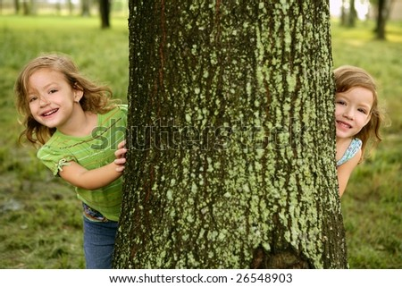 Two twin little sister girls playing on the park tree outdoor - stock photo